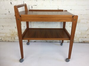 """Incredible Scandinavian modern teak bar cart in superb condition manufactured in the 1960's in Sweden. Features removable tray top with contoured corners to fit into the cart's flared edge, a sculpted handle and lower shelf, very nice quality craftsmanship all original, including castors - measures - 27""""W x 17""""D x 28""""H (SOLD)"""