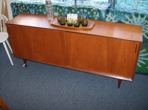 """Beautifully refinished Mid-century modern teak sideboard with 2 sliding doors and one drawer inside along with shelves on both sides - 65""""L X15.5""""D X28.5""""H - (SOLD)"""